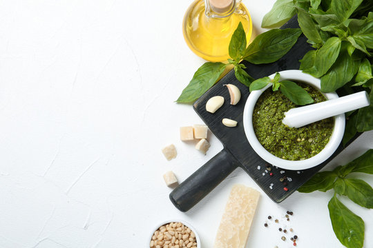 Flat lay composition with pesto sauce and ingredients on white table. Space for text
