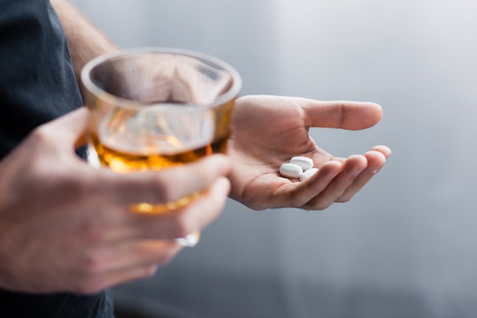 partial view of standing man holding handful of pills and glass of whiskey