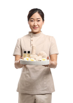 Professional masseuse in uniform holding tray with spa supplies on white background