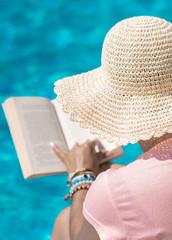 Podróżei wakacje w egzotycznych miejscach,  kobieta w słomkowym kapeluszu czyta książkę na...
