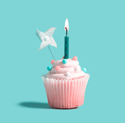 Celebratory cupcake with a decorative lit candle