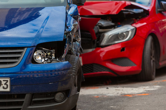 Close-up of two deformed Cars - red and blue - after a Car Crash, Collision, Accicent