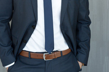 Torso of anonymous white collar worker standing with hands in pockets, wearing beautiful fashionable classic navy blue suit against grey backgound. Fotobehang