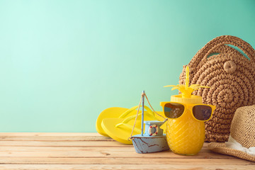 Summer vacation background with pineapple juice and beach accessories on wooden table