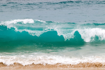 Wall Mural - Blue and aquamarine color sea waves and yellow sand  with white foam. Marine beach background.
