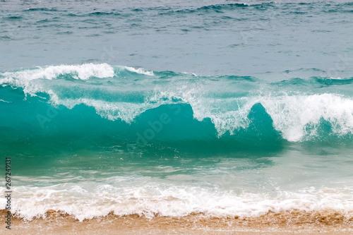 Wall mural Blue and aquamarine color sea waves and yellow sand  with white foam. Marine beach background.