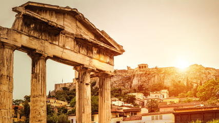 Roman Agora at sunset in summer, Athens, Greece. It is one of the top landmarks of Athens city. Sunny view of Ancient Greek ruins overlooking famous old Acropolis in the Athens center in sun light.