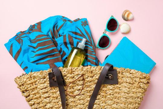 Summer beach bag with elegant women's accessories on pink background. Top view beach bag with dress, essential oil bottle, book, sunglasses. Flat lay stuff. Summer fashion, holiday vacation concept