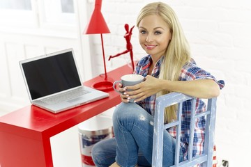 Casual young woman with laptop and cup of tea