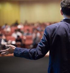 Rear view of man gesturing with hand while standing against defocused group of people sitting at the chairs in front of him. Business coach giving speech to audience in conference hall during lecture.