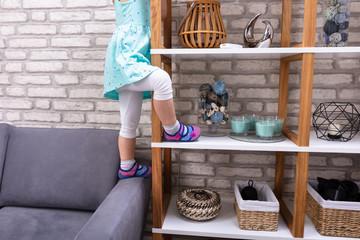 Girl Trying To Climb On Shelf