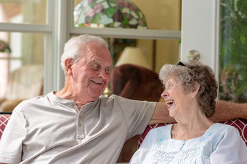 A beautiful senior couple in their seventies laughs while enjoying time together on their porch on a sunny day.