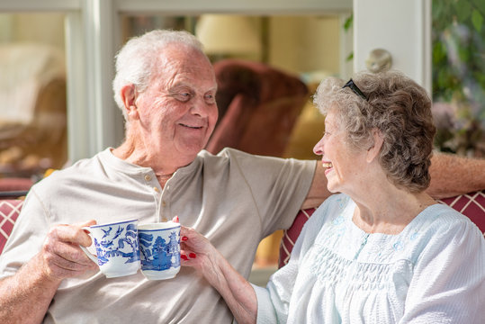 Senior woman looking at her husband. A beautiful senior couple in their seventies talks and laughs while they enjoy coffee or tea on their sunny porch one morning.