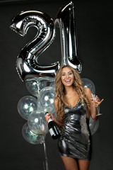 Beautiful young woman in party mini dress celebrating 21st birthday with champagne and balloons