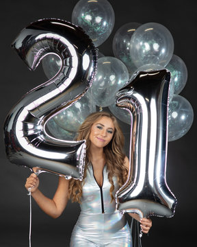 Beautiful young woman in party mini dress holding 21st birthday balloons