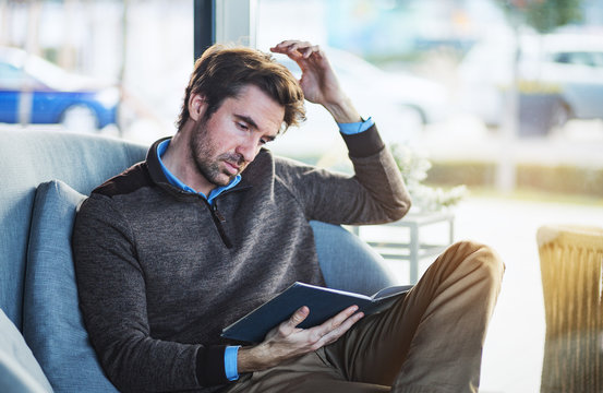 Handsome middle aged man sitting and reading book