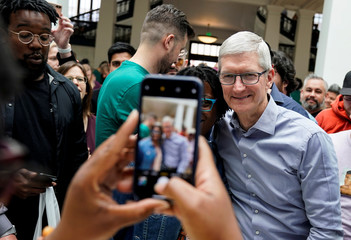 Apple Chief Executive Officer Tim Cook poses for a picture with a customer at the grand opening of the new Apple Carnegie Library store in Washington