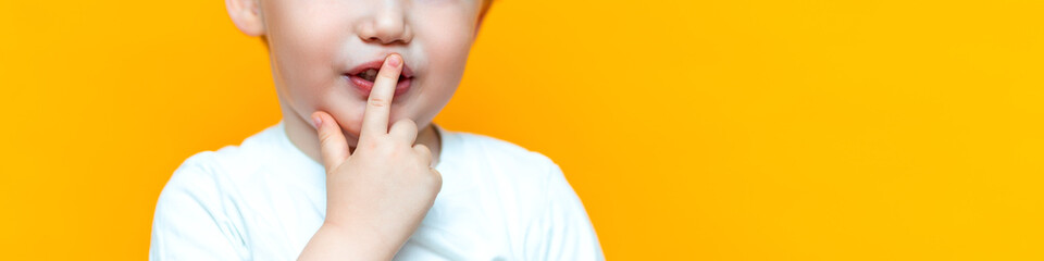 little boy child put his finger on lips, keep silence serious, blonde hair Wall mural