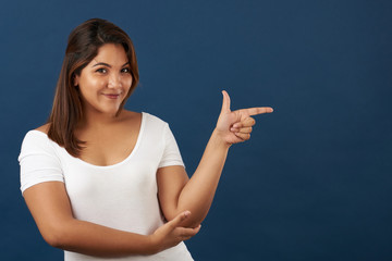 Young woman point finger in copy space