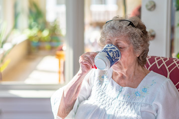 A beautiful senior woman enjoys her morning rituals on a sunny porch in her home.