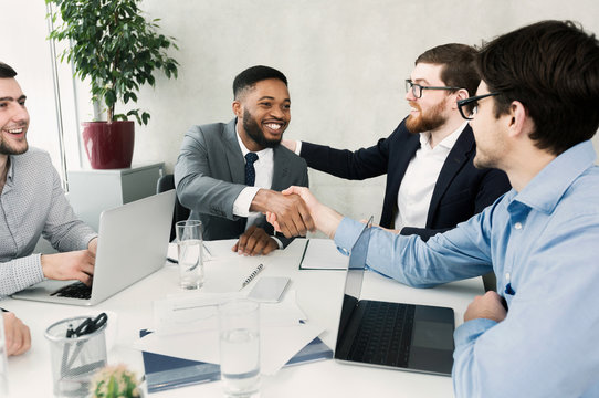 Happy team congratulating successful worker by shaking hands