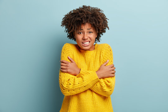 Scared fearful dark skinned woman trembles as afraids something awful, crosses hands over chest, clenches teeth, has Afro hairstyle, wears loose yellow sweater, models against blue background