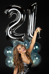 Beautiful young woman in party mini dress toasting 21st birthday with champagne and balloons