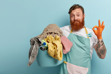 Satisfied bearded red haired man makes okay gesture, shows approval sign, says everything is under control, busy with daily routines, holds basin with dirty laundry, isolated on blue background