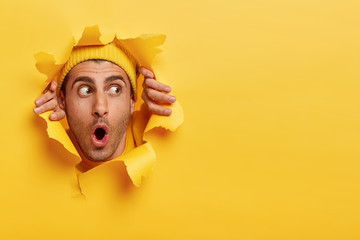 Surprised male face through paper hole. Emotional astonished young man wears yellow headgear, makes slot in background with hands, keeps mouth wide opened. Copy space to insert yout text or slogan Wall mural