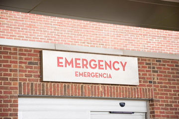 A prominent red emergency room signage with foreign language translation atop the automatic door...