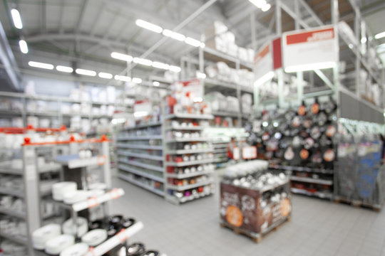 Blurred concept of DIY shopping center. Shelving with household products and kitchenware. Commercial LED lighting. Merchandising in retail.