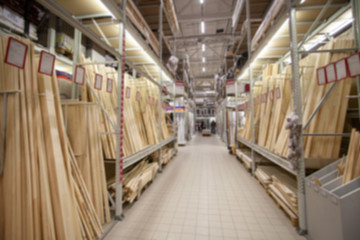 Sale in DIY shopping center. Lumber warehouse with wooden planks. Professional retail market for carpenter and builder. Blurred. Concept.