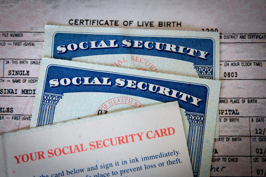wo USA Social Security cards with number obscured surrounded by US dollars or American dollars.  The SSN has become a de facto national identification number for taxation and other purposes.