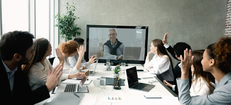 Business team having video call with senior boss at office