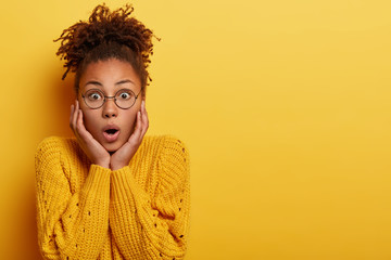 Speechless impressed woman learns terrible news, touches cheeks, keeps jaw dropped, has bugged eyes, wears transparent spectacles and knitted loose sweater, isolated over yellow wall. Monochrome