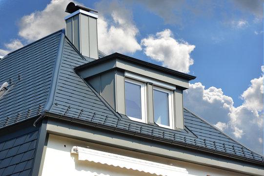 Mit Metallschindeln neu eingedecktes Haus mit metallverkleideter Schleppgaube und Schornstein sowie Dachrinne und Scheefang