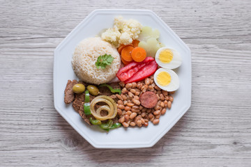 Brazilian food dish - Beans, rice, meat, eggs, salad