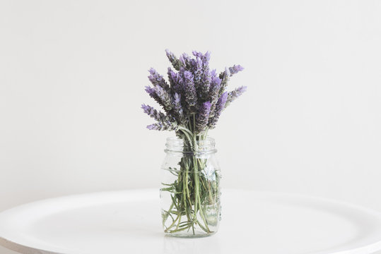 Close up of lavender in glass jar on small table against neutral wall background - matte filter effect and selective focus
