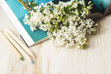 Spring romantic bouquet of a white lilac on the open book. Greeting card
