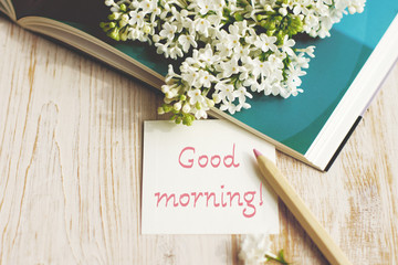 """Card for congratulation  with the inscription """"Good morning!"""" with white lilac flowers on the open book on a wooden background"""