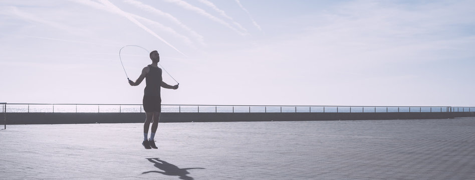 Muscular young man exercising with jumping rope on seafront