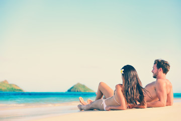 Wall Mural - Hawaii vacation couple relaxing on luxury holiday beach. Beautiful young adults in love on hawaiian holidays lying down on white sand. Copy space on blue sky background.