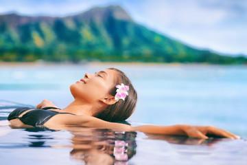Wall Mural - Hawaii vacation luxury resort travel Asian tourist girl relaxing in hotel infinity pool by Waikiki beach in Honolulu, Oahu. USA travel.