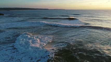 Wall Mural - Aerial view on big waves of Atlantic ocean and sunset sky, 4k
