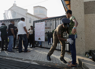 A police officer searches a worshipper at the main entrance of the St.Theresa's church as the Catholic churches in Sri Lanka restart their Sunday service after Easter Sunday bombing attacks on 21st of April,in Colombo