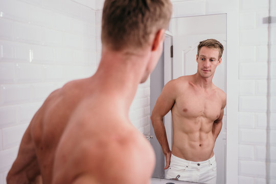 Portrait man muscle body at front reflection in the mirror in bathroom