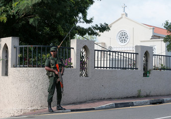 An army soldier stands guard at the main entrance of the St.Theresa's church as the Catholic churches in Sri Lanka restart their Sunday service after Easter Sunday bombing attacks on 21st of April,in Colombo