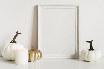 Front view composition with photo frame and white pumpkins. Copy space for artwork. Autumn decor in interior fragment