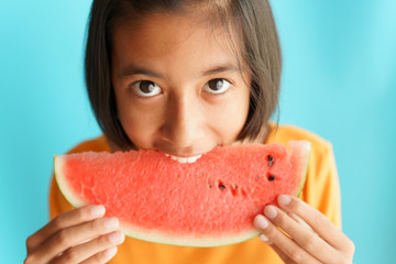 Portrait picture of asian little girl eating watermelon on blue background. A girl kid so happy after eat watermelon.