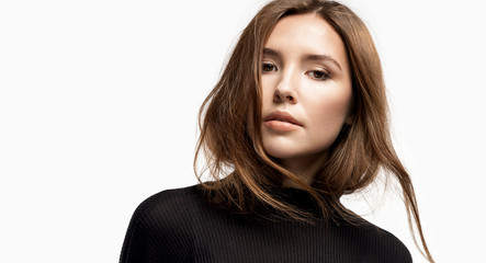 Close-up portrait of beautiful girl with perfect skin wearing black pullover. Charming young woman with natural beauty. Fashion and lifestyle concept. Isolated on white Wall mural